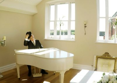 Simon Brown playing a white grand piano at a booking for Camscott Leisure
