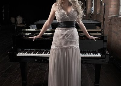 Image of Camscott Leisure pianist Jennie standing by a piano